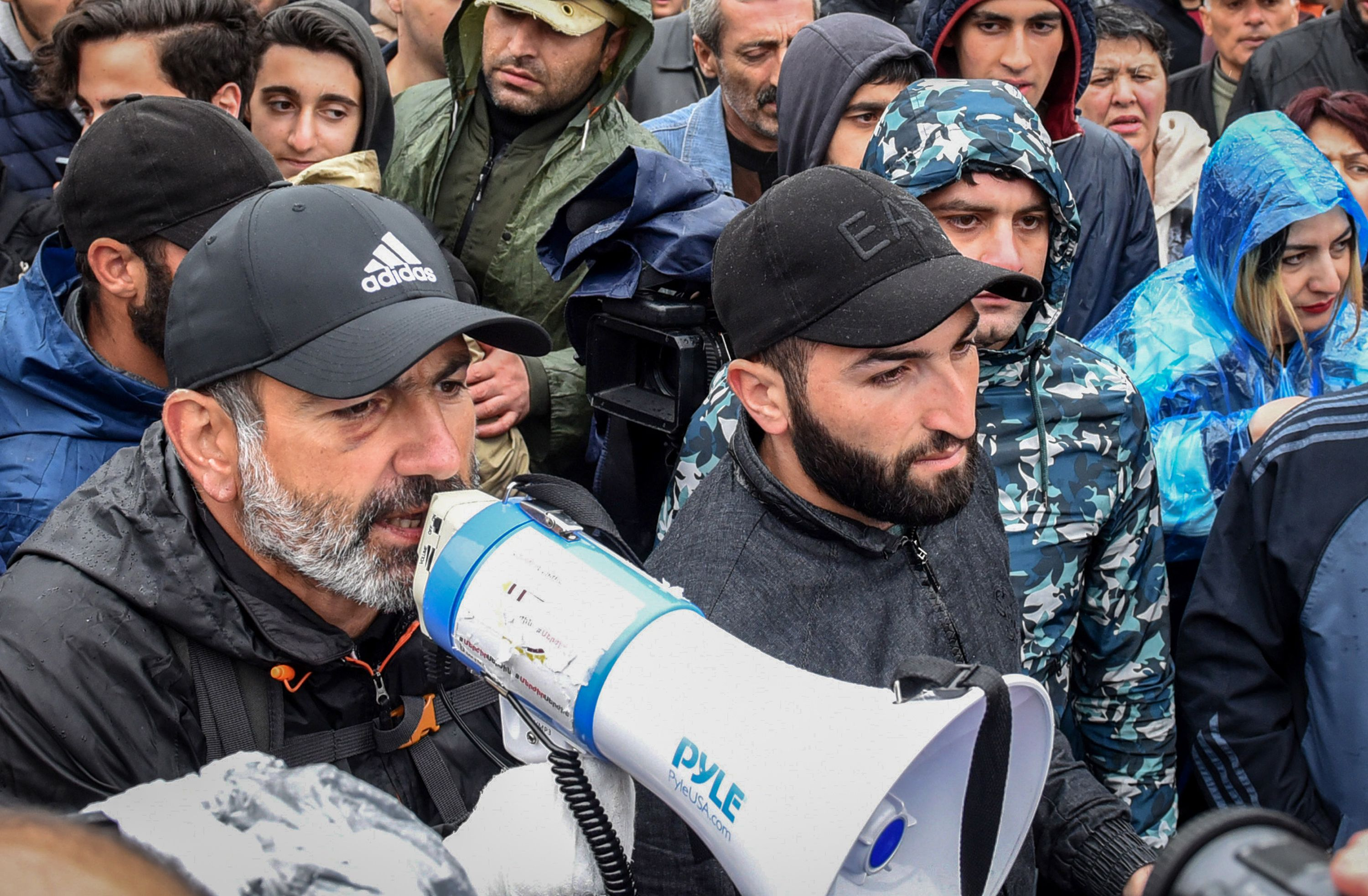 Armenian opposition leader Nikol Pashinyan (L) speaks through a megaphone during a rally in central Yerevan on April 21, 2018, held to protest the former president's election as prime minister. Armenia's political crisis deepened on April 21 as protest leader Nikol Pashinyan said he was only prepared to discuss the exit of the country's newly elected prime minister, former president Serzh Sarkisian.  / AFP PHOTO / Vano SHLAMOV