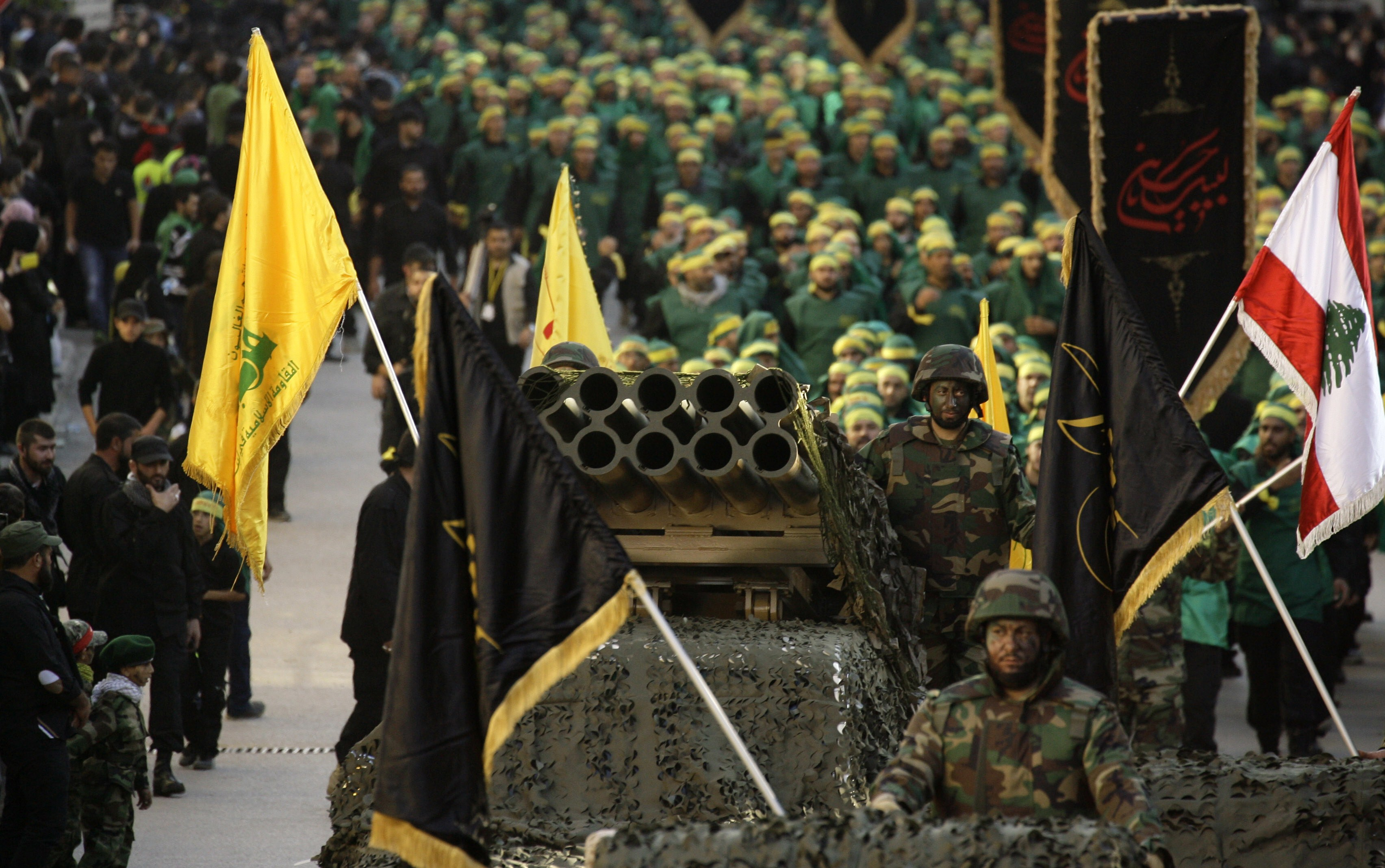 Members of Lebanon's militant Shiite Muslim movement Hezbollah stand on a pick-up truck mounted with a multiple rocket launcher as they take part in a parade in the southern city of Nabatiyeh on November 7, 2014, to mark the 13th day of Ashura, where believers mourn the killing of the Prophet Mohammed's grandson, Imam Hussein, during the battle of Karbala in central Iraq in the seventh century. AFP PHOTO / MAHMOUD ZAYYAT        (Photo credit should read MAHMOUD ZAYYAT/AFP/Getty Images)