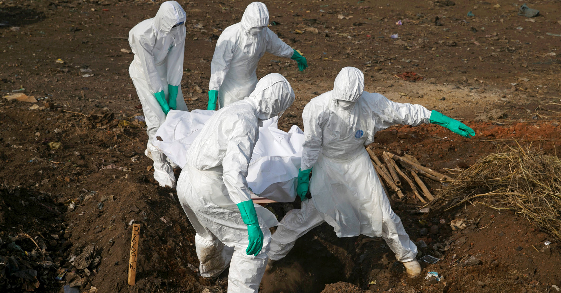 Health workers carry the body of a suspected Ebola victim for burial at a cemetery in Freetown, Sierra Leone, December 21, 2014. To match Special Report HEALTH-WHO/LEADER REUTERS/Baz Ratner/File Photo